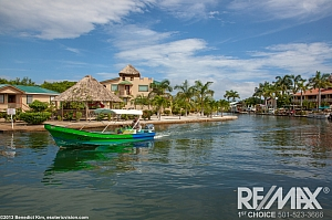 Placencia Pointe With Local Skiff Passing